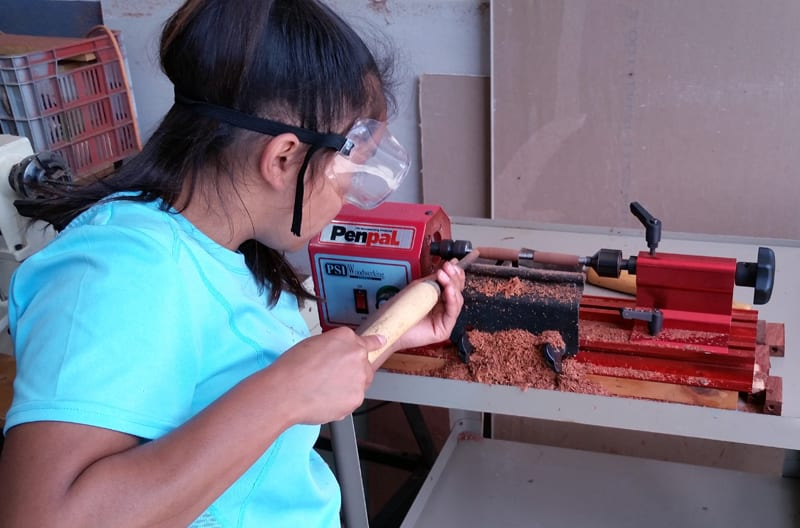 One of our teenage girls making wooden pens on a lathe