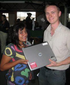Tim giving a laptop to Regina
