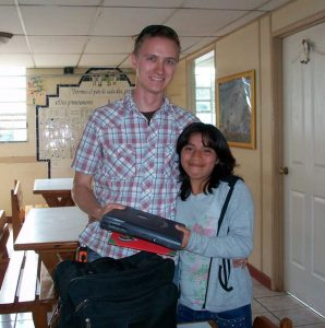 Tim giving a laptop to Sandra, one of the first students we had, as she left for college